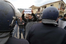 A protestor holding a placard telling President Abdelaziz Bouteflika to step out of the way at a demonstration held in Bejaia on 5 April 2014 to call for a boycott of the Algerian presidential election. (AP Photo/Sidali Djarboub)