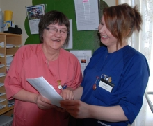 Two health admin staff looking at a paper and smiling