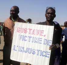 Two men holding a sign saying Gustave, victim of injustice