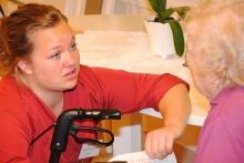A young care worker with an elderly patient
