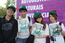 Four people with Robin Hood Tax hats and posters