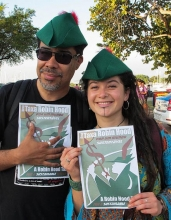 A couple  holding Robin Hood Tax posters and wearing Robin Hood caps