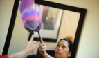 Woman dusting off mirror