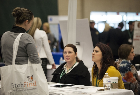 Unemployed person talks to advisors at a job fair
