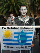Man dressed as clown holding banner against water privatisation